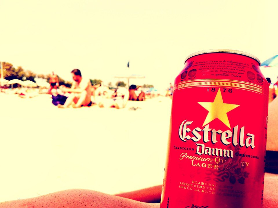 A close up of a bright red can of Estrella Damm on the beaches of Barceloneta, Barcelona