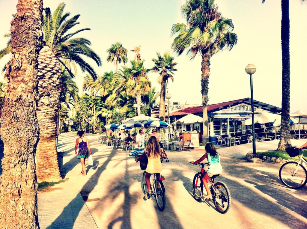 girls cycling along the promenade in Sitges Barcelona