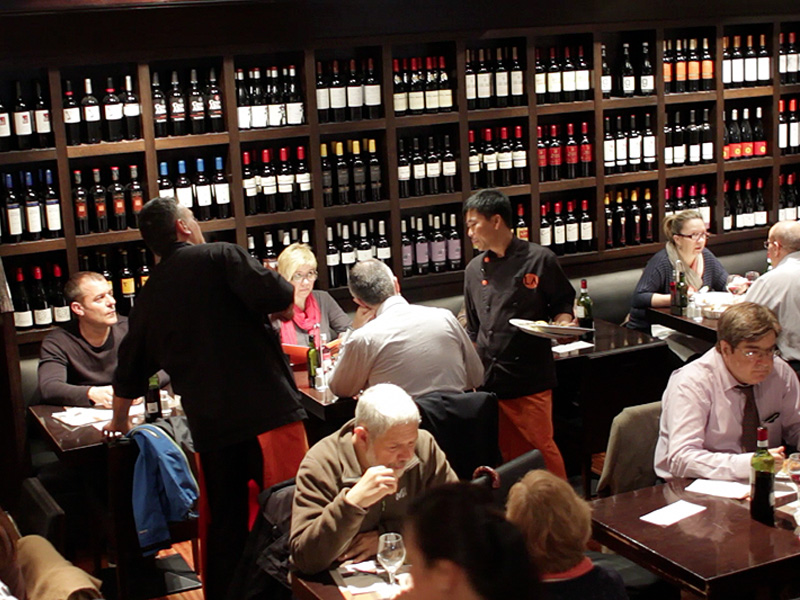 walls lined with beautiful bottles of wine and waiters serving tapas in Barcelona