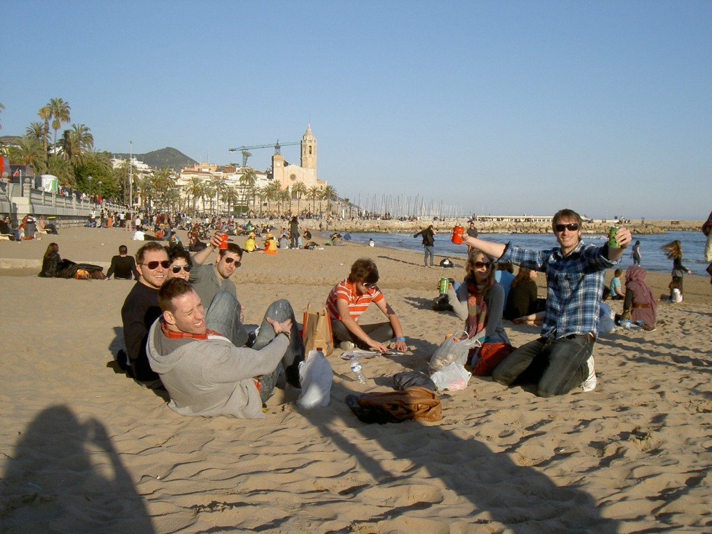 Friends drinking cold beers at Sitges beach, just outside of Barcelona