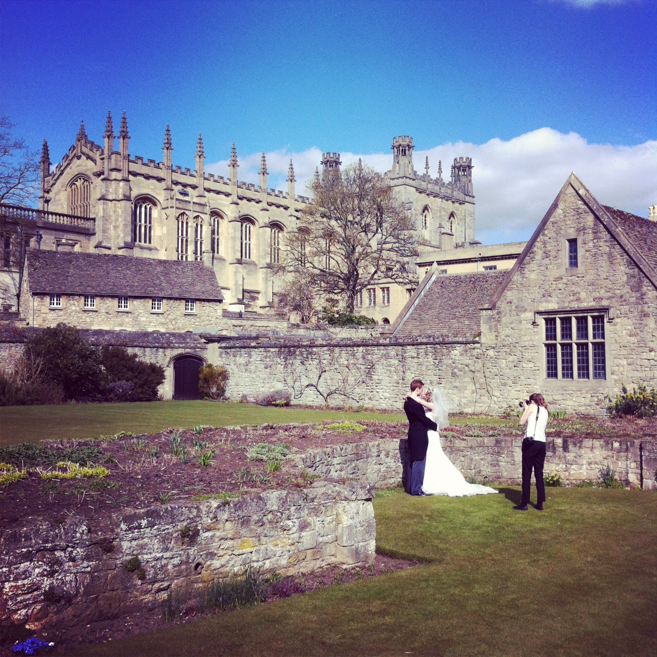 Bride and groom being photographed outside of Christchurch College in Oxford