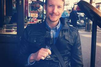 Travel writer Ben Holbrook sips on wine in Paris