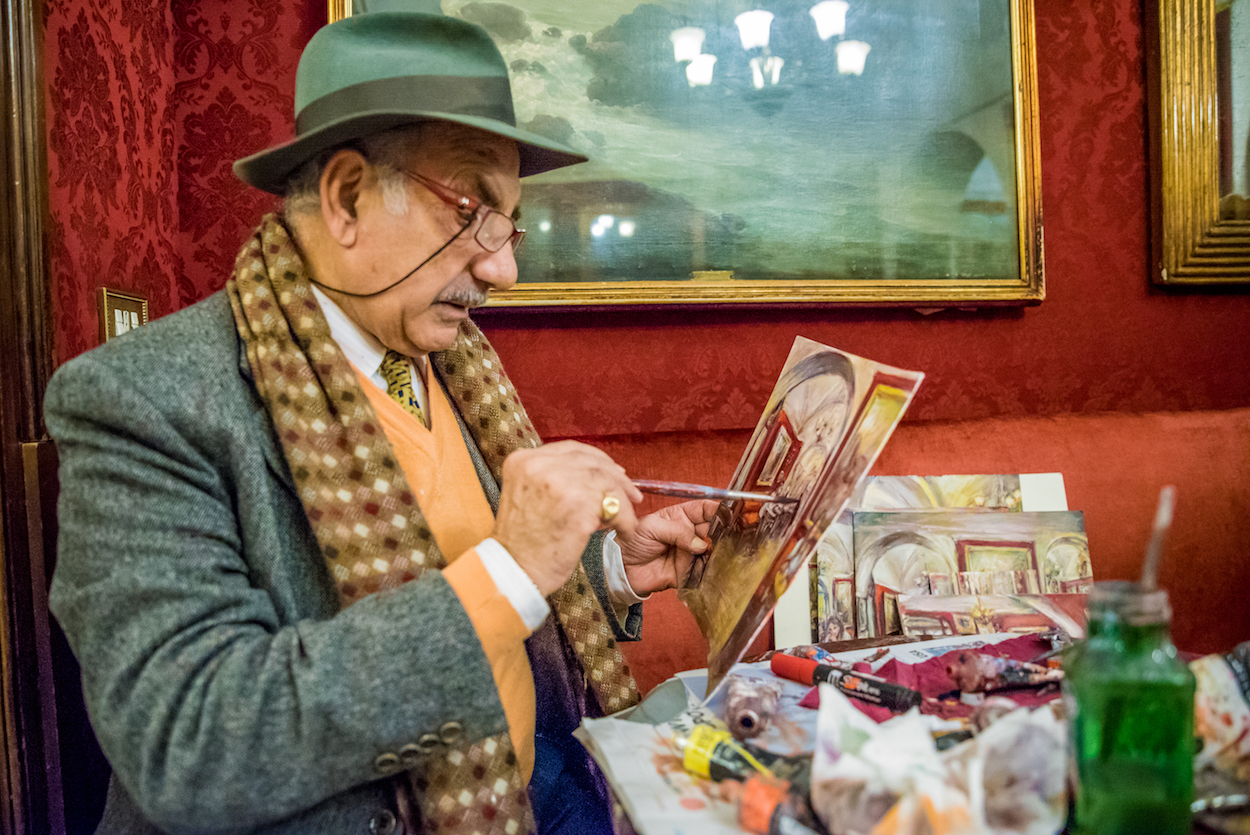 An artist painting at Antico Caffè Greco - Rome's oldest cafe.