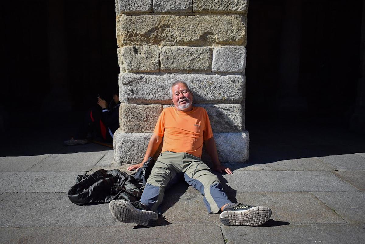 An exhausted pilgrim in Praza do Obradoiro, Santiago de Compostela - by Ben Holbrook